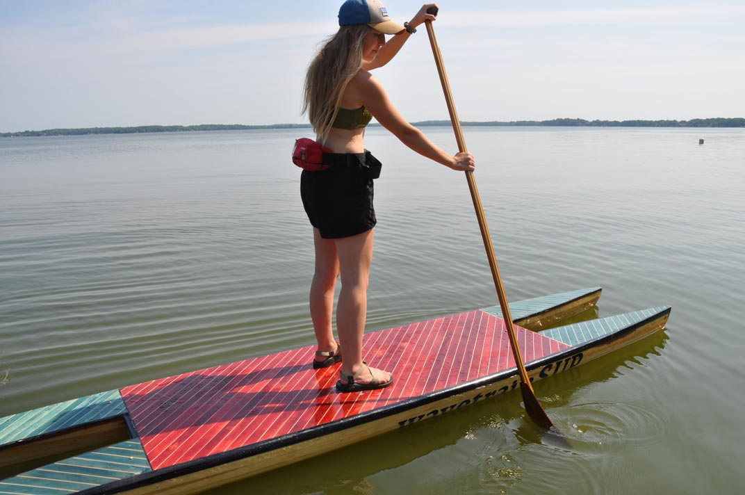 picture of a paddleboard featuring two pontoons and a deck.